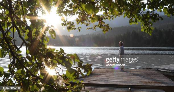 man walks onto dock over lake and watches sunrise over mountains and forest - early retirement stock pictures, royalty-free photos & images