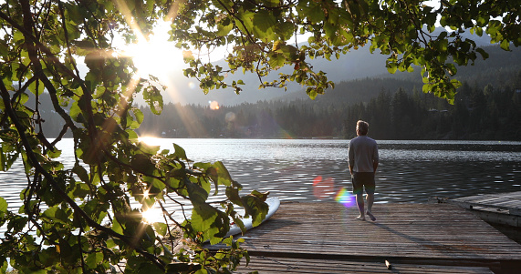 Man walks onto dock over lake and watches sunrise over mountains and forest 1167385734
