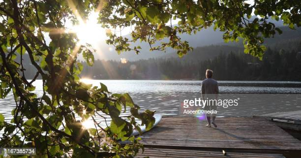 man walks onto dock over lake and watches sunrise over mountains and forest - tranquil scene stock pictures, royalty-free photos & images