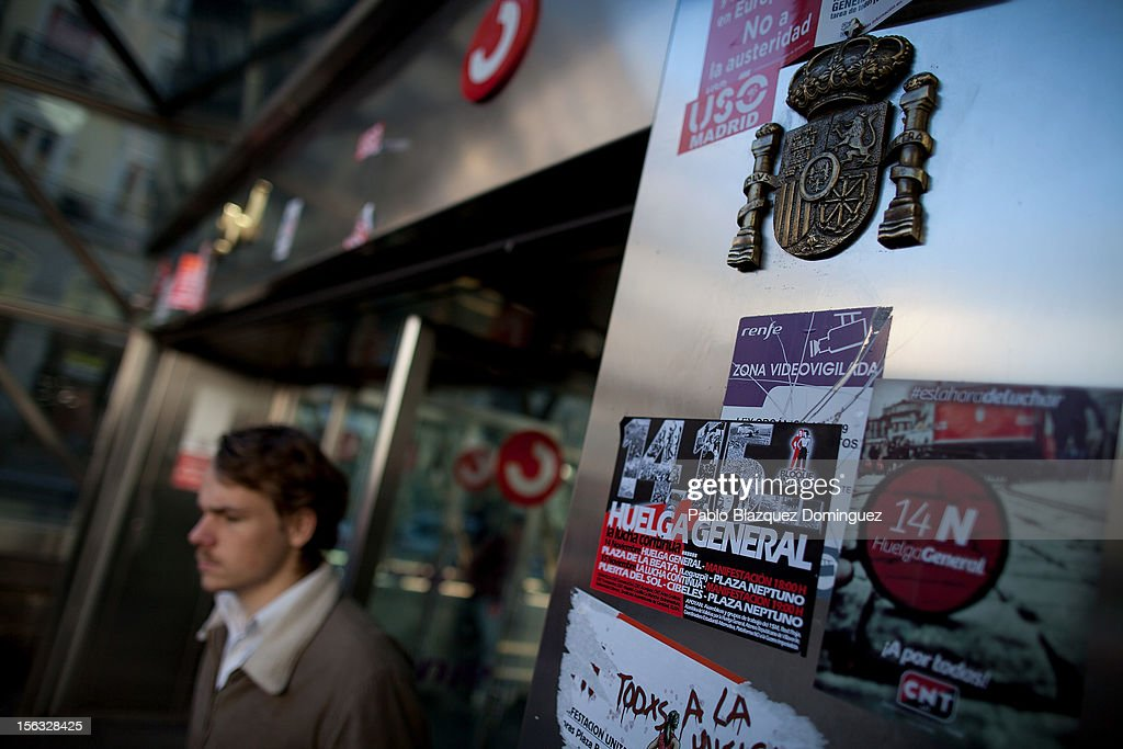 A man walks out from Sol Station next to a Spanish shield and stickers that read 'N14 General Strike' on November 13, 2012 in Madrid, Spain. Spain's trade unions have called a general strike for November 14, the second general strike during Mariano Rajoy's presidency. Protestors from social movements are expected to join striking public sector workers to protest against austerity cuts and labour reforms. Spain's unemployment rate has now reached 25 per cent.