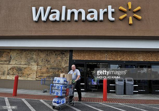 Man walks out of a boarded up Walmart store with a cart full of bottled water and other supplies in Kitty Hawk in the North Carolina Outerbanks on...