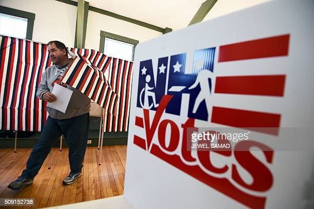 TOPSHOT A man walks out of a booth with his ballot for the first US presidential primary at the town hall in Canterbury New Hampshire on February 9...