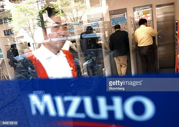 Man walks out of a Mizuho bank branch while people use ATM machines in central Tokyo Thursday, April 21, 2005.