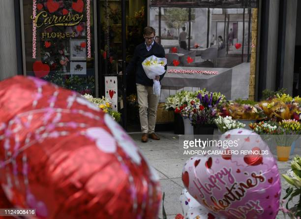 A man walks out of Caruso Florist with a bouquet of flowers on Valentines Day in Washington DC on February 14 2019