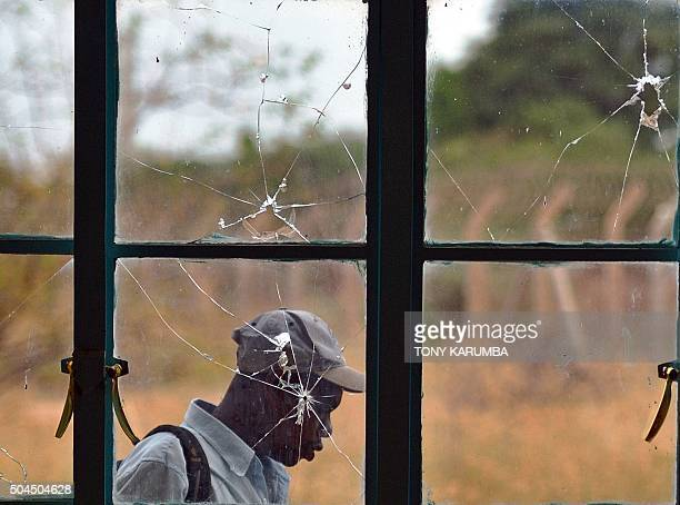 TOPSHOT A man walks outside a lecture hall with bulletshattered window panes in Garissa university on January 11 2016 Students trickled back on...