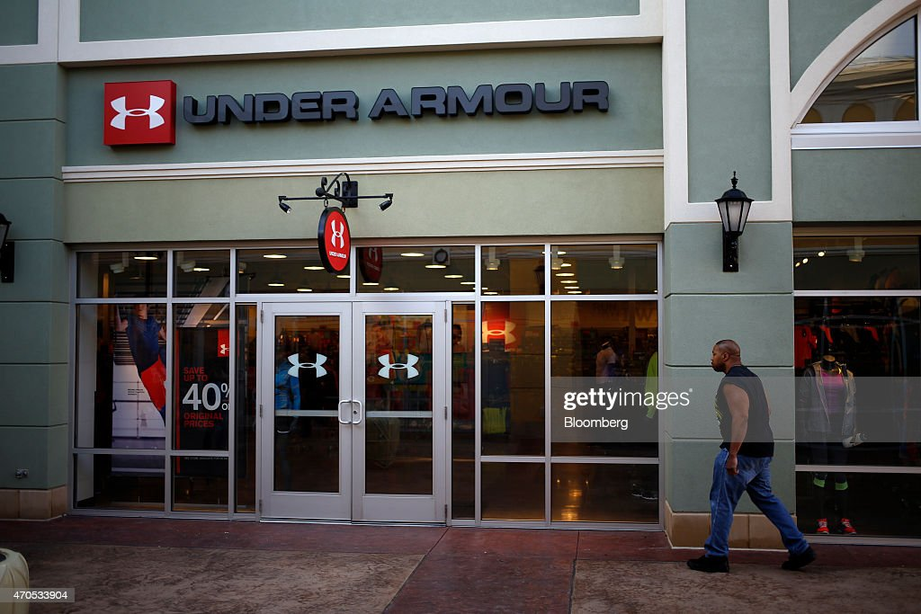 A Man Walks Outside An Under Armour Inc. Store At The Outlet Shoppes Of The