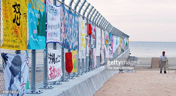 A man walks outside the newly set up fence where antiUS base slogans are hung at US Marine Corps Camp Schwab on May 14 2011 in Nago Okinawa Japan