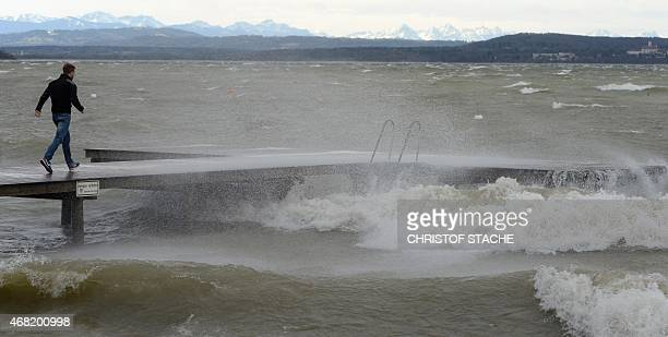 A man walks over a bridge at the lake Ammersee in the small Bavarian village of Herrsching southern Germany as stormy weather hits the country on...