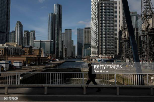 Man walks over a bridge near the Canary Wharf business district on February 12, 2021 in London, England. The ONS figures released today show that the...