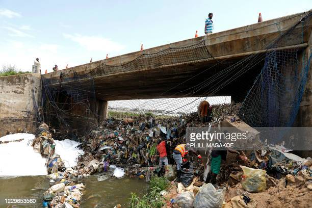 A man walks over a bridge while workers from Freshngo remove plastic deluge from litter trap nets and long line cables that was washed down the...