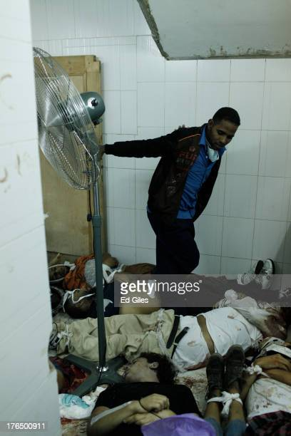 Man walks over the bodies of supporters of deposed Egyptian President Mohammed Morsi lie on the floor of the Rabaa al-Adaweya Medical Centre in the...