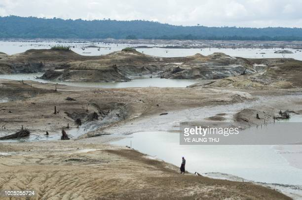 A man walks over the dried ground of the Swar Chaung dam after water level decreased when the spillway collapsed at Swar township Bago region on...