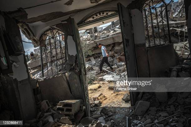 Man walks over the rubble of a residential building in Gaza City, Gaza Strip, that was destroyed by an Israeli airstrike, on May 13, 2021 in Gaza...