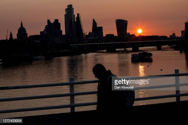 Man walks over Waterloo Bridge at sunrise on September 14, 2020 in London, England. Many companies with headquarters in London's city centre have...