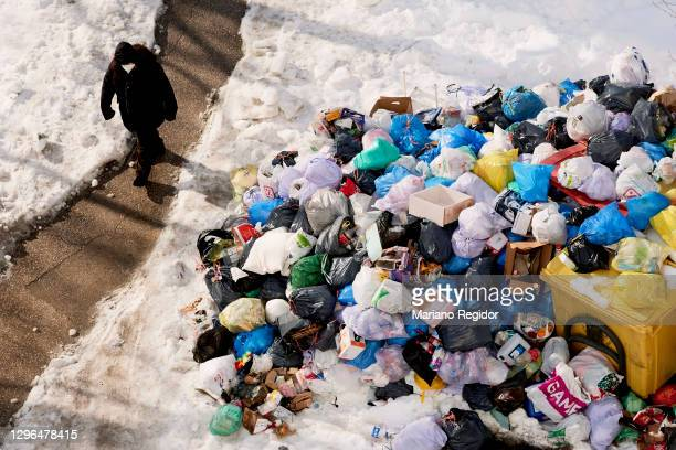 Man walks pass accumulated garbage in the streets of Madrid due to the snow caused by storm Filomena on January 15, 2021 in Madrid, Spain. After...