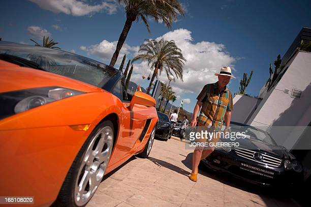 A man walks pass luxury cars in Marbella on March 30 2013 AFP PHOTO / JORGE GUERRERO