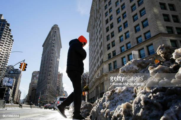 A man walks pass snow accumulated on the sidewalk as the Flatiron Building is pictured during freezing temperatures on January 07 2018 in New York...