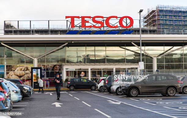 Man walks pass TESCO logo and supermarket in Wales. The new, highly contagious strain of the virus has taken a firm foothold in Wales. One in four...