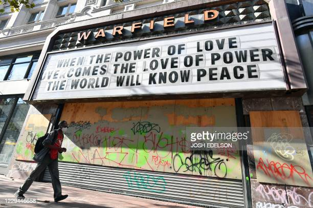A man walks passed a motivational sign posted at a boarded up theater in San Francisco California on November 3 2020 The US started voting Tuesday in...