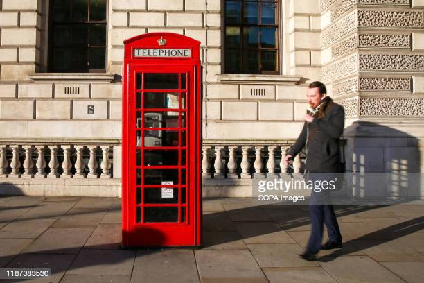 A man walks passed the 'Red' telephone box in Westminster