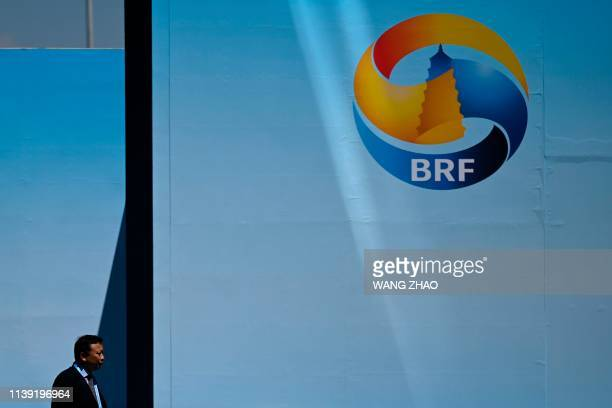 A man walks past a a billboard for the Belt and Road Forum at the entrance to the China National Convention Centre in Beijing on April 25 2019...