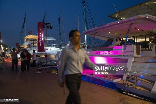 A man walks past a Alegria 67 catamaran manufactured by Fountaine Pajot SA moored during the Singapore Yacht Show at Sentosa Cove in Singapore on...