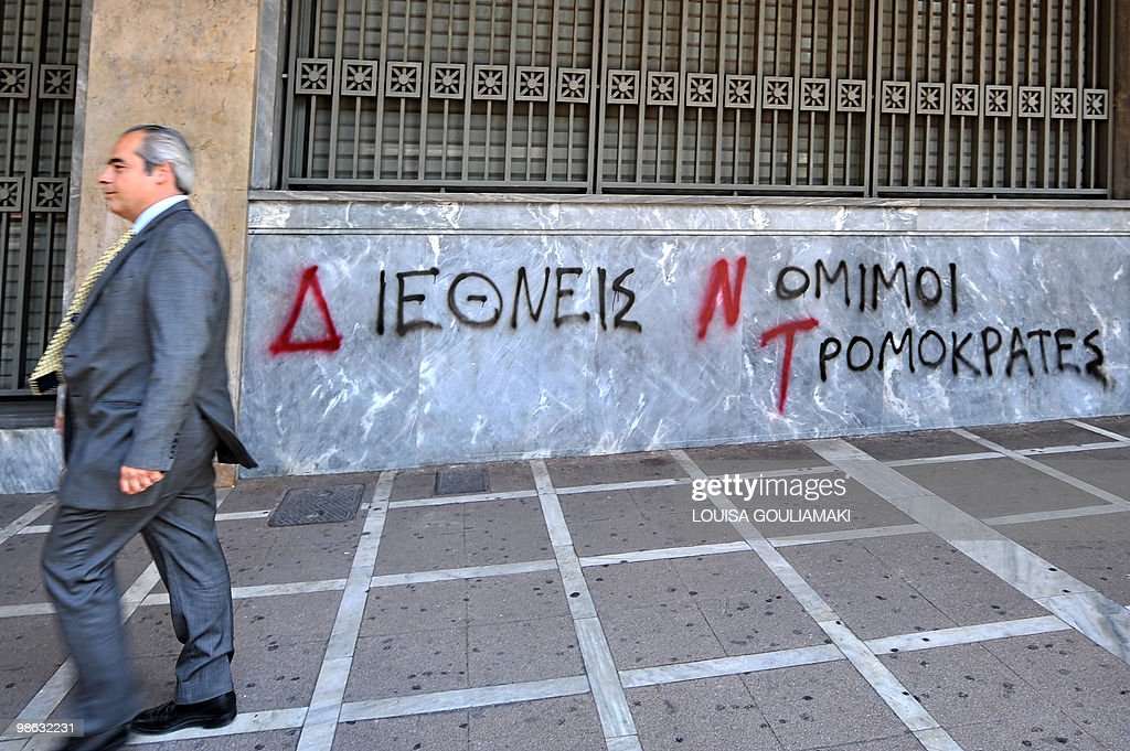 A man walks past a 'Bank of Greece' as a graffiti reads on the wall 'IMF, 'International Legal Terrorists' in Athens on April 23, 2010.Greece appealed for a debt rescue from the EU and IMF on Friday and said that help should arrive within days, in a dramatic turn for the eurozone at risk from Greek contagion. Prime Minister George Papandreou told his nation in a televised speech that the aid was a 'national need' which would 'offer us a safe port to allow our boat to float again.'