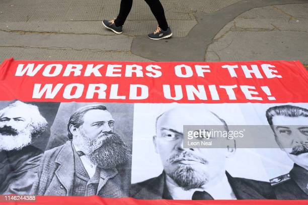 A man walks past a banner as British Union members prepare to take part in the Labour Day March on May 1 2019 in London England The Labour Day March...