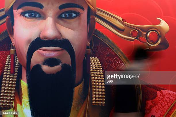 A man walks past a banner showing the Chinese god of wealth at the G2E Asia gaming expo in Macau on May 22 2012 Casino industry leaders gathered in...