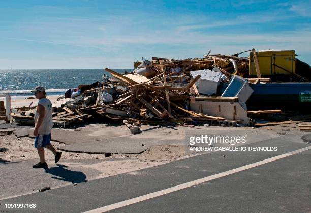 A man walks past a bar that he worked in destroyed by a storm surge near Port Saint Joe Florida on October 12 two days after hurricane Michael hit...