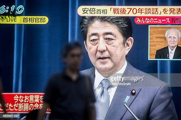 A man walks past a big screen showing a live broadcast of Japanese Prime Minister Shinzo Abe as he delivers his WWII Anniversary Statement on August...