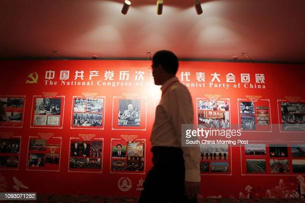 Man walks past a bill board displaying historical pictures of the previous 18th National Congress of the Communist Party of China at the Media Centre...