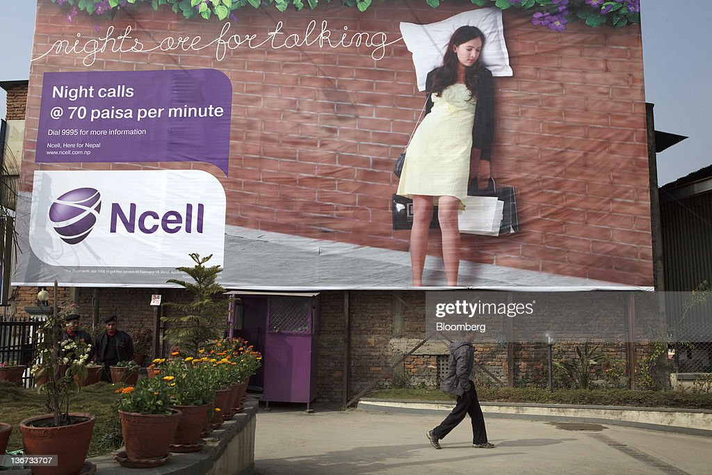 A man walks past a billboard advertisement for Ncell Pvt  Ltd  in