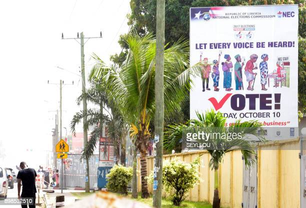 A man walks past a billboard as the nation prepares to vote in upcoming national elections on December 25 2017 in Monrovia Liberians choose a new...