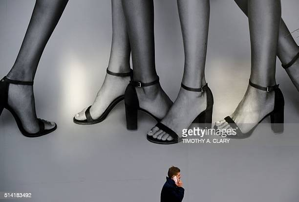 Man walks past a billboard for Stuart Weitzman shoes on 5th Avenue in New York City March 7,2016. / AFP / Timothy A. CLARY