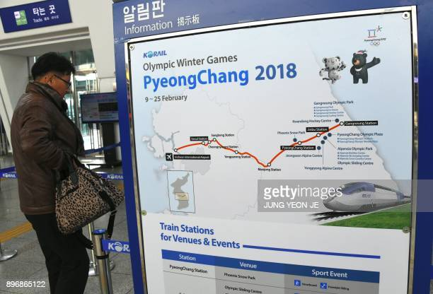 Man walks past a billboard showing information of a new high-speed train line for the 2018 PyeongChang Winter Olympic Games, at Seoul station in...