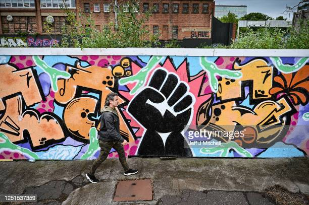 Man walks past a black lives matter mural by artist Boss City Taio on June 23, 2020 in Glasgow, Scotland. Black Lives Matter protests are continuing...