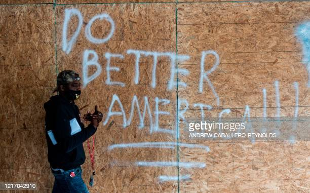 A man walks past a boarded up shop after the unrest from the past few nights in downtown Washington DC on June 2 2020 Antiracism protests have put...