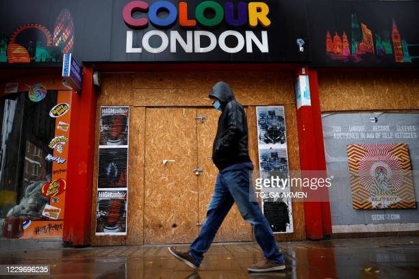 Man walks past a boarded up shop in central London on November 20 as life under a second lockdown continues in England. - The current lockdown in...