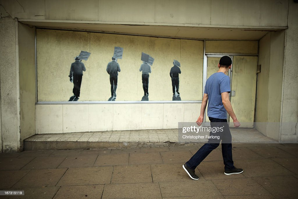 A man walks past a boarded up shop with artwork depicting Corby's steel heritage on April 24, 2013 in Corby, England. A recent study pin pointed Corby as Britain's youth unemployment capital. The study by education specialists Ambitious Minds found that youth unemployment was 11% rising from 4% in 2007. Corby in Northamptonshire was built around its steel industry in the 1930's. The steel works closed in 1980 with the loss of 10,000 jobs.