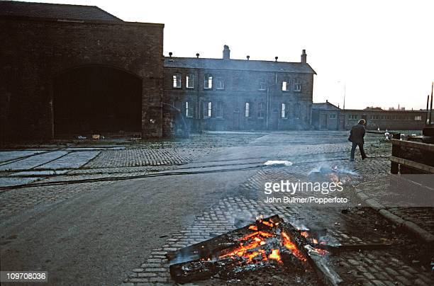 A man walks past a bonfire in a street in Manchester England in 1976