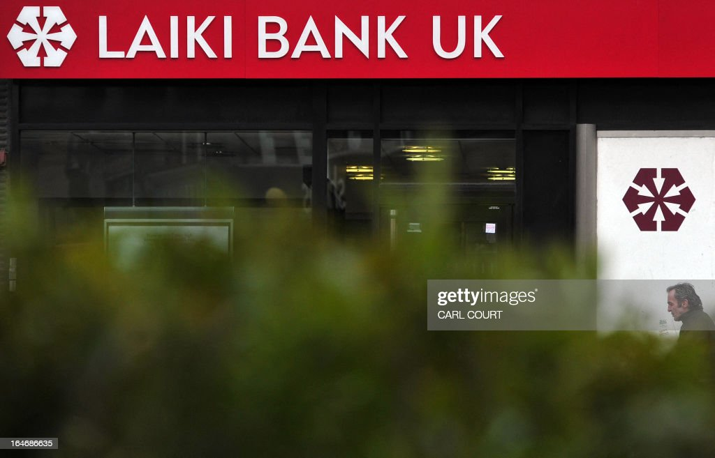 A man walks past a branch of Laiki Bank UK, a subsiduary of Cyprus Popular Bank (Laiki Bank), in north London on March 26, 2013. British Chancellor of the Exchequer George Osborne revealed the government was in negotiation with Cyprus to find a solution regarding branches of Cyprus Popular Bank (Laiki Bank) in Britain. Cyprus's second largest bank Laiki will wind up in Cyprus under a painful restructuring plan that was a condition of the eurozone bailout.