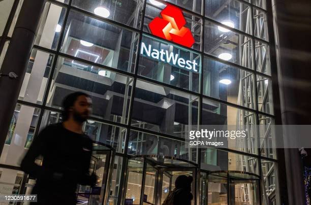 Man walks past a branch of NatWest Bank in London.