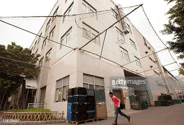 A man walks past a building surrounded by safety netting at the Longhua Science Technology Park also known as Foxconn city in Shenzhen China on...