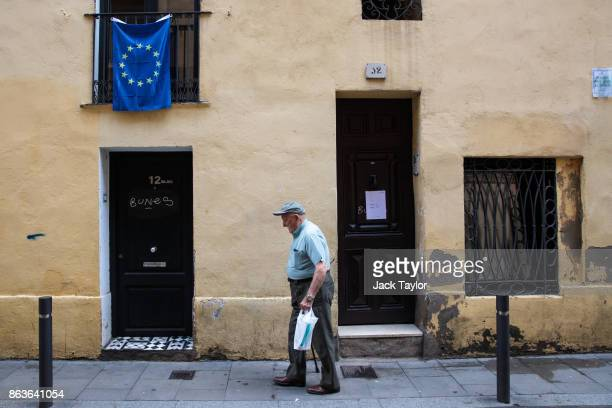A man walks past a building with a European flag hanging from a balcony on October 20 2017 in Barcelona Spain The Spanish government is to take steps...