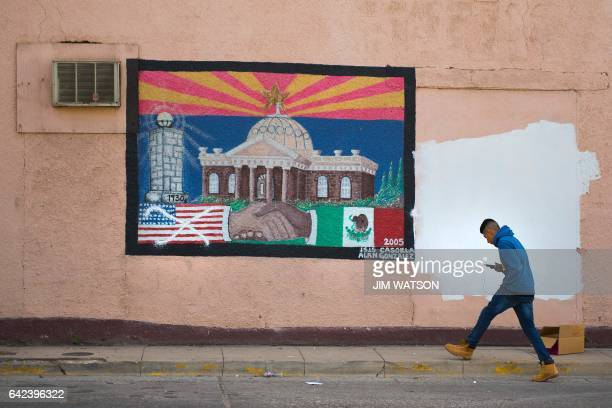 A man walks past a burial of US/Mexico cooperation in which the American flag has been crossedout in Nogales Arizona on February 17 on the US/Mexico...