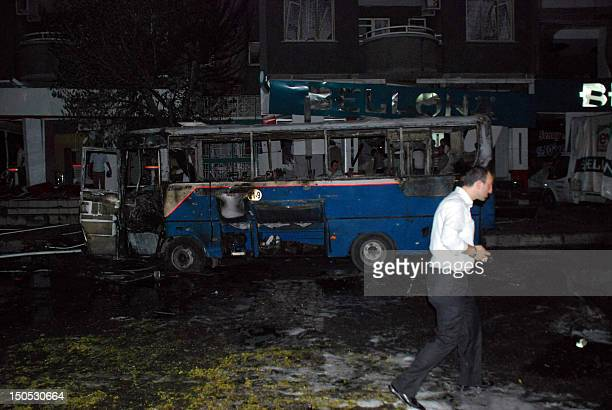 A man walks past a burned bus where at least seven people were killed and dozens wounded when a car bomb blew up on August 20 2012 in the centre of...