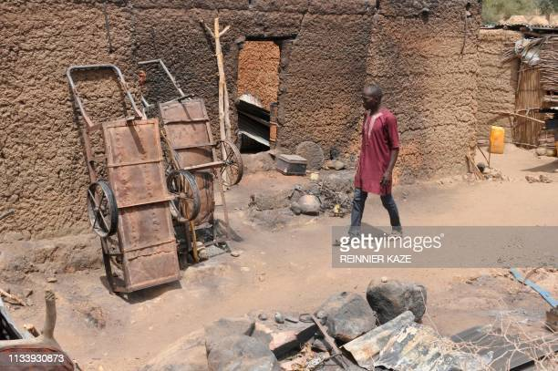 A man walks past a burned house in Zeleved northern Cameroon on March 23 2019 Since 2014 Boko Haram fighters have been striking on the region located...