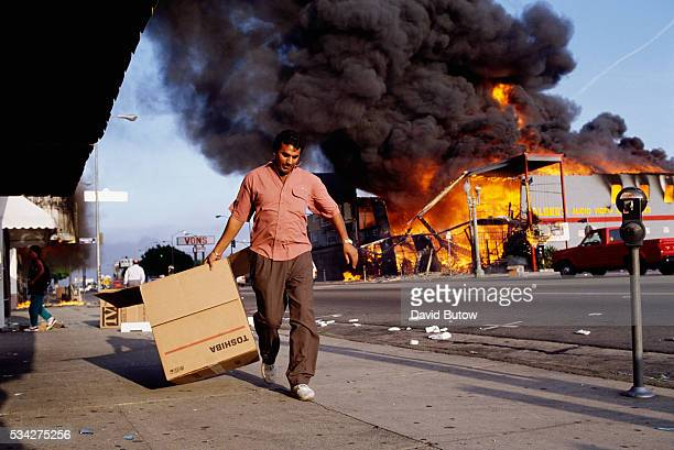 A man walks past a burning building during the Los Angeles riots In April of 1992 after a jury acquitted the police officers involved in the beating...