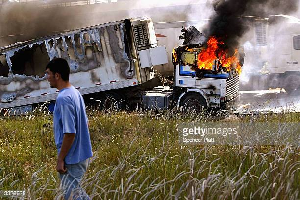 A man walks past a burning truck that was part of a US military convoy that came under attack on April 10 2004 in Baghdad Iraq Much of Iraq is still...